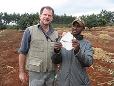 Thika, Kenya Expedition - Worker displaying the hole in a roof piece from one of the greenhouse smashers.