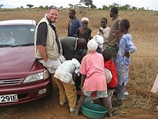 Thika, Kenya Expedition - Local kids removing Black Jacks from Mike's boots.