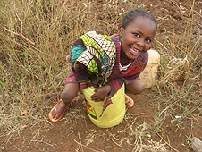 Thika, Kenya Expedition - Little girl sitting on a bucket making us laugh.